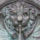 Close-Up of Lion Fountain in Austria. Close-up photograph of lion head and mane in water fountain in the city of Kufstein, Austria, made of aged copper Stock Photos