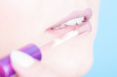 Close-up of lips with brush applying glossy lipgloss Royalty Free Stock Photo