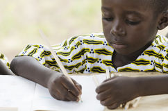 Close-up of little African boy studying and drawing. Young boy sitting at table and writing on paper with pencil Stock Photo