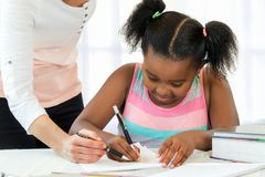 Caucasian teacher helping little black girl with maths. Close up of little african girl doing school work with caucasian teacher supervising Royalty Free Stock Photo