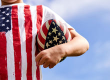 Close-up of little American boy holding rugby ball. Close-up of little American boy wearing t-shirt with stars and stripes holding rugby ball in hand royalty free stock image