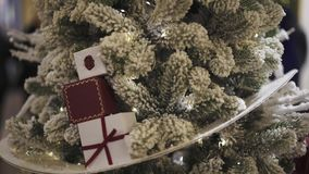 Close up of little artificial christmas fir tree in snow with small gift boxes. Close up gimbal pan shot of little artificial christmas fir tree in snow with stock video footage