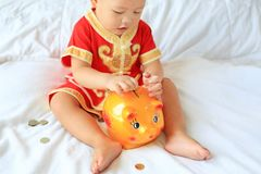 Close up little Asian baby boy in traditional Chinese dress putting some coins into a piggy bank sitting on bed at home. Kid. Saving money concept. Focus at royalty free stock photos