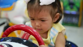 Close up of little asian baby girl learning to drive an arcade car game - babies explore new fields in their lives. Close up of little asian baby girl, 20 months stock footage