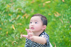 Close-up little Asian boy looking up somewhere and thinking with. Some hope, hand raise up, at outdoor playground, shallow DOF Royalty Free Stock Photo