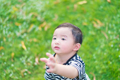 Close-up little Asian boy looking up somewhere and thinking with. Some hope, hand raise up, at outdoor playground, shallow DOF Stock Image