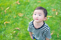 Close-up little Asian boy looking up somewhere and thinking with. Some hope, at outdoor playground, shallow DOF Royalty Free Stock Photography