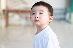 Close-up little Asian boy looking up somewhere and thinking with. Close-up little Asian boy in white t-shirt looking up somewhere and thinking with some hope Stock Photo