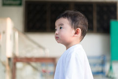 Close-up little Asian boy looking up somewhere and thinking with. Close-up little Asian boy in white t-shirt looking up somewhere and thinking with some hope Royalty Free Stock Images