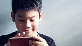 Close up of Little asian boy playing and smile ,sit in room , Tilt up camera stock video footage