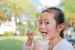 Close-up little Asian child girl eating yogurt in park stock photo