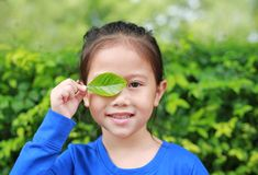 Close up little Asian child girl holding a green leaf closing right eye in green garden background.  stock photo