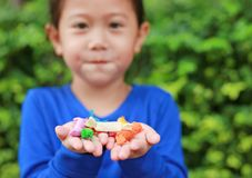 Close-up little Asian child girl holding some thai sugar and fruit toffee with colorful paper wrapped in her hands.  royalty free stock images