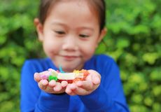 Close-up little Asian child girl holding some thai sugar and fruit toffee with colorful paper wrapped in her hands.  stock photos