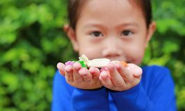 Close-up little Asian child girl holding some thai sugar and fruit toffee with colorful paper wrapped in her hands.  stock image