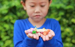 Close-up little Asian child girl holding some thai sugar and fruit toffee with colorful paper wrapped in her hands.  royalty free stock photos