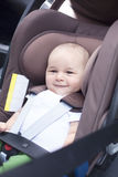 Close up of little baby boy in a car in a child seat. Close up of cheerful little baby boy in a car in a child seat Stock Images