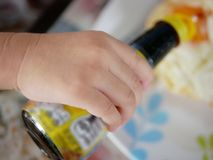 Close up of little baby`s hand holding a bottle of soy bean sauce stock images