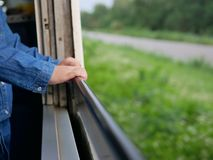 Close up of little baby`s hands holding on a frame of an opened window on a traveling train. Travel has made the babies more curious and instilled in them a royalty free stock photo
