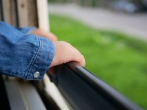 Close up of little baby`s hands holding on a frame of an opened window on a traveling train. Travel helps the babies become adaptable and more flexible royalty free stock photography