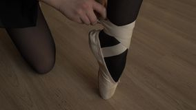 Close-up of the little ballerina wears Pointe shoes. Female feet in pointe shoes. Pointe shoes worn by ballet dancer stock video