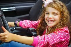 Close up of little beatiful smiling girl sitting in the car pretending to drive the luxury black car, weaing a pink Royalty Free Stock Images