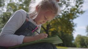 Close up Little beautiful school girl drawing with colored pencils, sitting on a bench in sunny park. Slow Motion Shot. stock video footage
