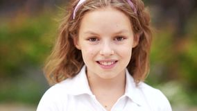 Close up of a little blonde brown-eyed cute girl face. Girl blinking her eyes and smiling. Inside. Portrait shot. Happy stock footage