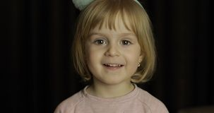 Close up of a little blonde cute girl face. Girl smiling. Inside. Portrait shot royalty free stock photo