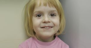 Close up of a little blonde cute girl face. Girl smiling. Inside. Portrait shot royalty free stock image