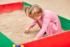 Little girl in a pink dress in a sandbox. Stock Image
