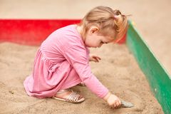 Little girl in a pink dress in a sandbox. Royalty Free Stock Image