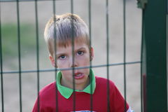Close up of a little boy behind a fence Stock Image
