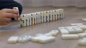 Little boy playing with dominoes on the floor of the house. Domino principle.
