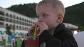 Close-up of a little boy drinking juice in the evening in cafe at the hotel. stock footage