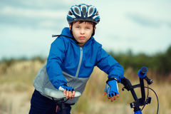 Close-up of a little boy face on bike looking at Stock Image