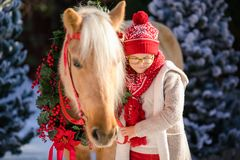 Close-up little boy with glasses and adorable pony with festive wreath near the small wooden house and snow-covered trees. New Yea stock photo