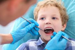 Close-up of little Caucasian curly boy opening his mouth wide during inspection of oral cavity by dentist. Close-up of little boy opening his mouth wide during Royalty Free Stock Images