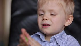 Upset boy three years playing with colorful dough. Close-up of little boy playing house with colorful dough stock footage