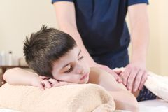 Close up A little boy relaxes from a therapeutic massage. Male massage therapist makes a medical massage to the back of. A child stock photography