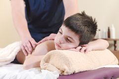 Close up A little boy relaxes from a therapeutic massage. Male massage therapist makes a medical massage to the back of. A child royalty free stock image