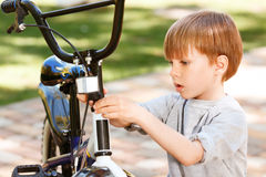 Close up of little boy repairing his bike Stock Image