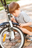Close up of little boy repairing his bike Royalty Free Stock Photography