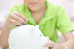 Close up Little boy saving money in piggy bank Royalty Free Stock Image