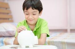 Close up Little boy saving money in piggy bank Stock Photos