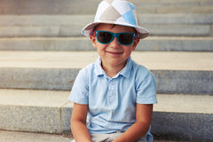 Close-up of little boy in sunglasses and hat sitting on concrete Stock Photos