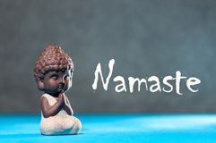 Close-up of little buddha meditating, focus on arms in Namaste gesture and text namaste - yoga and zen concept.  stock images