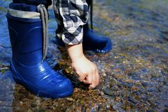 CLOSE UP OF LITTLE CHILD WEARING BLUE RAINBOOTS AND PLAYING WITH royalty free stock image