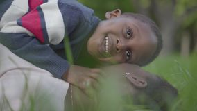 Close-up of little cute African American boy lying on top of his mother, playing with her earring and smiling. Mother. Close-up of little cute African American stock video