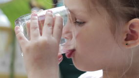 Close-up of a little cute girl drinking pure water from a glass. Outdoor